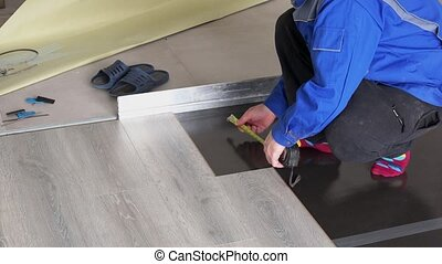 Man with ruler meter measure laminate length on floor....