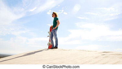 Man with sand board looking at a distance in the desert 4k