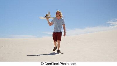 Man with sand board walking in the desert 4k