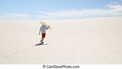 Man with sand board walking in the desert on a sunny day 4k