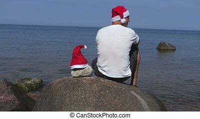 Man with Santa Claus hat on stone near the sea