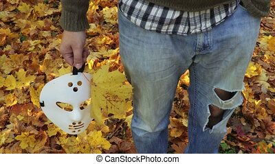 Man with scary Halloween mask and autumn leaves