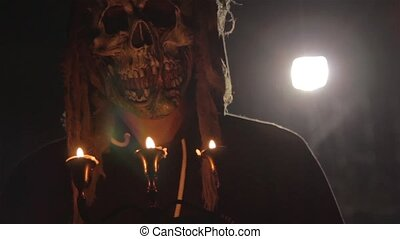 Man with scary halloween mask holding candles back lit by light. Black magic ritual or scary halloween rite