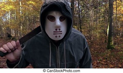 Man with scary Halloween mask look into the camera and...