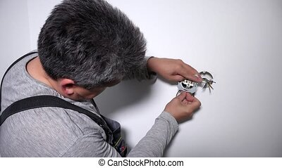 Man with screwdriver screw electrical outlet on wall. ...