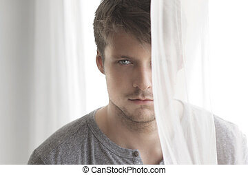 Man with secret - Portrait of a young man near window with...