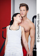 Man With Seductive Woman Standing In Gym