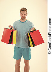 Man with shopping bags isolated on white. Macho with colorful paper bags. Fashion shopper in casual blue tshirt and shorts. Holidays preparation and celebration. Shopping during sale and black friday