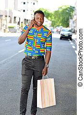 man with shopping bags talking on smart phone