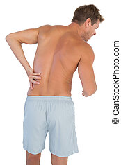 Man with shorts suffering from lower back pain on white ...