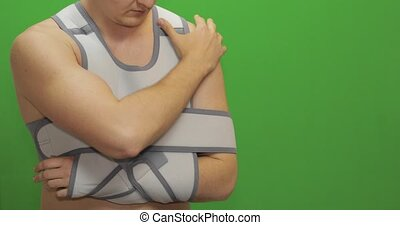 Man with shoulder injury. Nurse with syringe with medicines makes prick from pain. Patient in a bandage for fixing of an elbow joint and a humeral belt. Arm brace