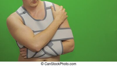 Man with shoulder injury. Nurse with syringe with medicines makes prick from pain. Patient in a bandage for fixing of an elbow joint and a humeral belt. Dislocations of arm of the forearm, shoulder