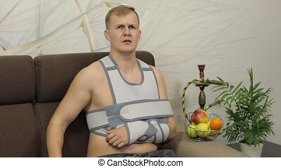 Man with shoulder injury. Painful, bored man with a broken arm wearing arm brace sitting on a sofa at home. Patient in a bandage for fixing of an elbow joint and a humeral belt. Slow motion