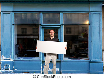 Man with sign by shop - Man standing with a blank sign by a...