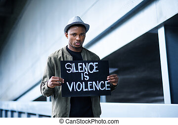 Man with silence is violence sign standing outdoors, black ...