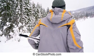 man with skis under his arm rises to the mountain preparing...