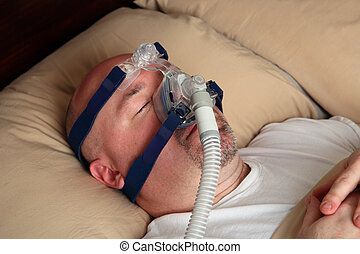Man with sleep apnea using a CPAP machine - Caucasian man ...