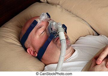 Man with sleep apnea using a CPAP machine - Caucasian man...