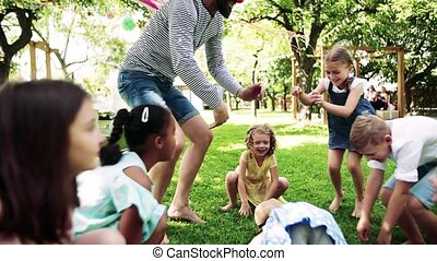 Man with small children sitting on ground outdoors in garden...