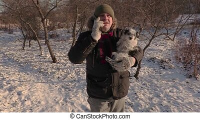 Man with small dog on hands talking on smart phone