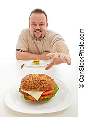 Man with small hamburger reaching for a bigger one