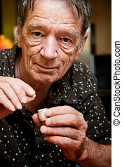 Senior man with small pill and metal container