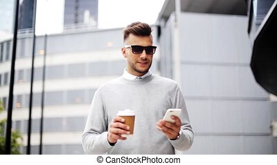 man with smartphone and coffee cup on city street