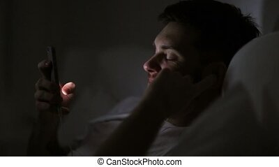 man with smartphone and earphones in bed at night -...