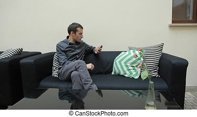 Man with Smartphone and Sitting on Couch