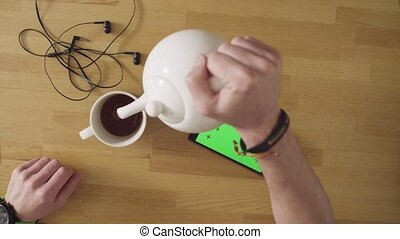 Man with smartphone drinking tea
