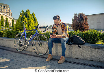 Man with smartphone sitting on street near bicycle