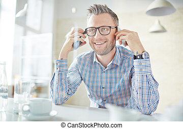 Man with smartphones - Smiling businessman in eyeglasses...