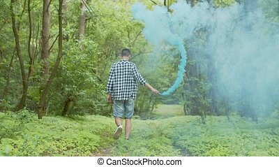 Man with smoke bomb walking through summer forest - Back...