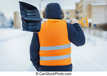 Man with snow shovel near building