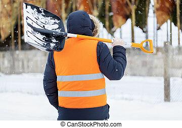 Man with snow shovel near tanks