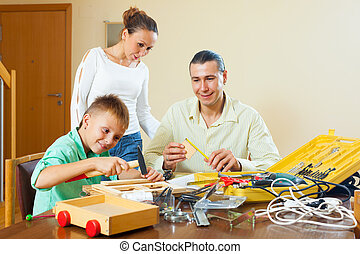Man with son doing something with the working tools