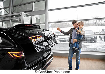 Man with son on hands observing auto in showroom.