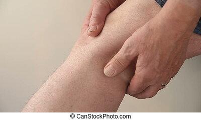 man with soreness behind knee - a man checks the pain at his...