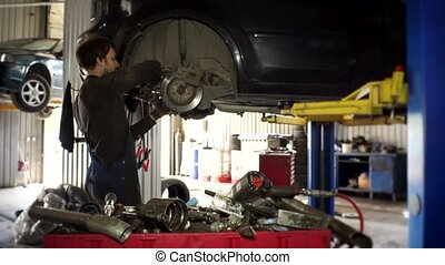 Man with spanner tool unscrew brake discs of used car....