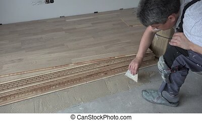 Man with spatula apply wood adhesive on concrete floor. Oak...