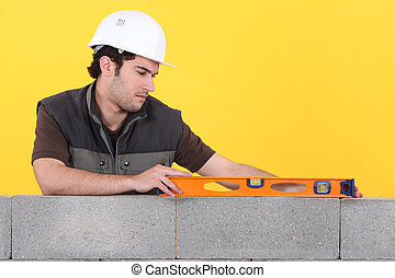 Man with spirit level checking wall