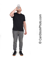 man with sportswear drinking water on white background
