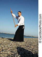 Man with stick exercising aikido