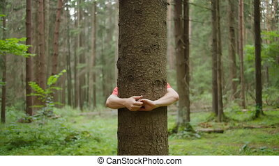 A man with strong hands hugs a tree trunk, nature conservation, environmental protection, unity with nature