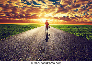 Man with suitcase and hat on long straight road towards sunset sky