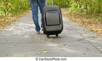 Man with suitcase walking on pavement