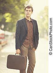 Man with suitcase walking outdoors
