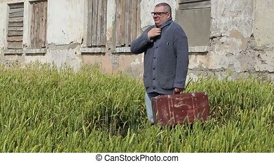 Man with suitcase yawning near abandoned building