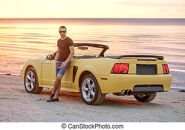 Man with super car on back of sunset - Man standing by his...