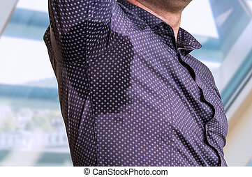 Man with sweating under armpit in business office